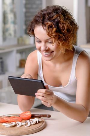 tabla de surf: Navegar por internet. Primer plano de alegre sonriente atractiva mujer joven sosteniendo portátil y apoyado en la mesa mientras se cocina
