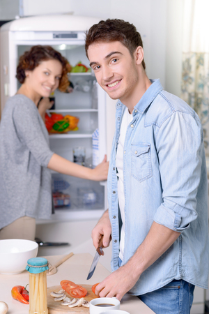 nice face: Happy family. Pleasant elated handsome man cutting vegetables and cooking while his wife opening the fridge in the background