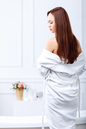 rob: Sensual body. Pleasant attractive young woman wearing rob and feeling content while going to take shower Stock Photo