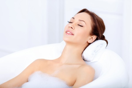 and harmony: Feel harmony. Pleasant content beautiful woman closing her eyes and feeling glad while taking a bath Stock Photo