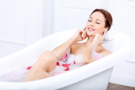 bañarse: Siente el ritmo. Contenido de Niza mujer encantadora que toca sus oídos y escuchar música mientras toma un baño Foto de archivo