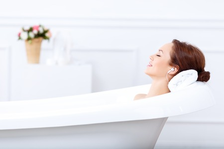 Just relax. Content beautiful young woman listening to music and closing her eyes while taking a bath 스톡 콘텐츠