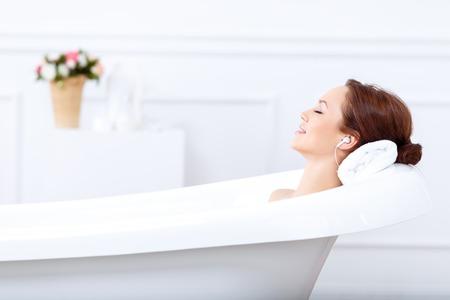 armonia: Relájate. Contenido bella mujer joven escuchando música y cerrando los ojos mientras tomaba un baño