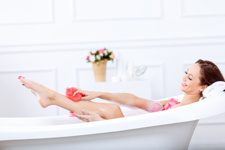 upbeat: stay beautiful. Pleasant smiling upbeat woman holding sponge and holding it on her leg while taking a bath