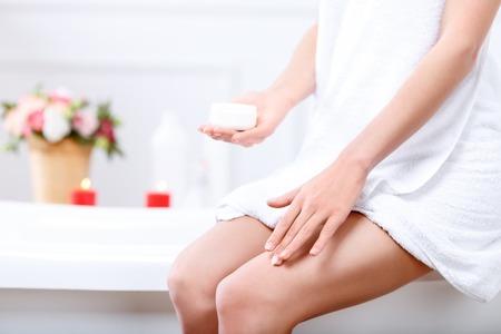 bañarse: Por siempre bella. Cerca de las piernas de agradable atractiva chica delgada que cubre las piernas con crema después de tomar un baño