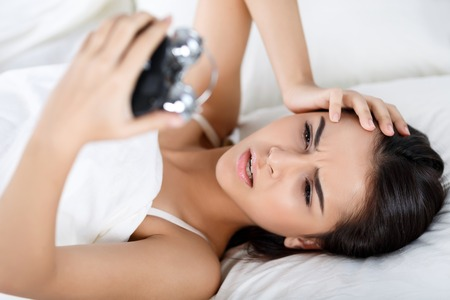 oversleep: Do not oversleep again. Disappointed pleasant young appealing woman holding alarm clock and touching her head while lying in bed Stock Photo