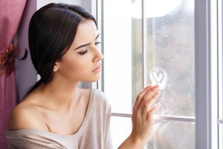 mujer sola: Los quiero mucho. Agradable hosca hermosa chica triste sentado en el alféizar de la ventana y la pintura sobre vidrio a la espera de su corazón el amor Foto de archivo
