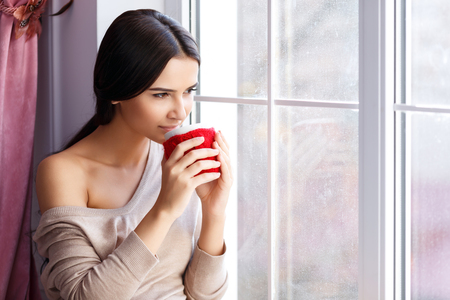 joyless: Favorite drink. Nice charming content young woman sitting on the window sill and holding cup while reveling in drinking tea