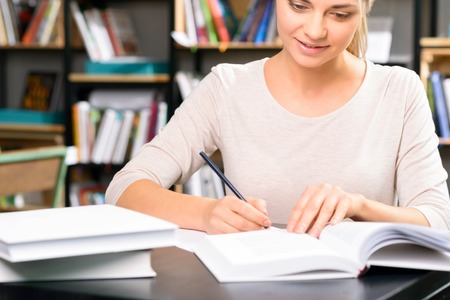 assignments: Homework time. Appealing young female student is sitting at the desk and doing her various home assignments. Stock Photo