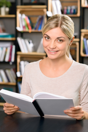 charmingly: Interesting textbook. Pleasing young woman is looking up from her textbook and smiling charmingly.