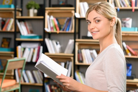 research facilities: Time to read. Smiling attractive young woman is standing and holding a small book. Stock Photo