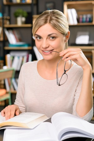 charmingly: Joyful time. Radiant young woman is sitting at the library desk and smiling charmingly.