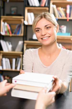 returning: Research finished. Young beautiful woman is smiling while returning all books to the library. Stock Photo