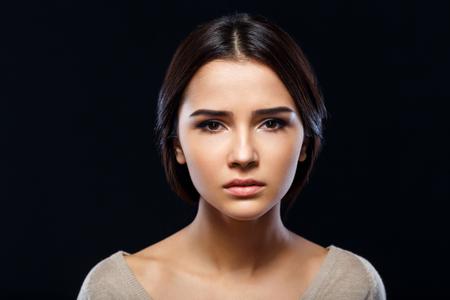 Primer plano de una mala mujer joven deprimida triste pidiendo ayuda y va a llorar, mientras que de pie aislado en el fondo negro