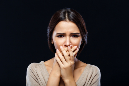 Joyless depressed upset girl holding her hands on the face and crying while standing isolated on black background