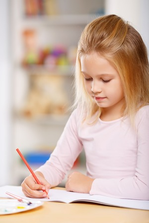 one room school house: Lovely little girl looks busy with drawing at the table.