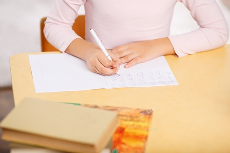 one room school house: Lovely schoolchild is sitting at the desk and writing capital alphabet letters. Stock Photo