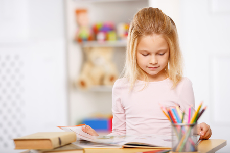 one room school house: Reading time. Charming little girl is standing beside the desk and reading a fairytale.
