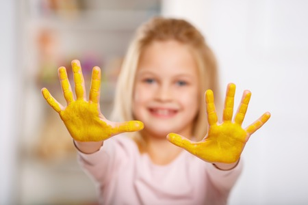 one room school house: Cheerful little girl demonstrating her palms covered in yellow gouache. Stock Photo
