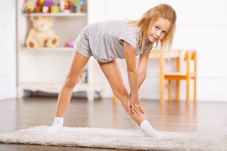 one room school house: Lovely little child is busy doing physical exercises.