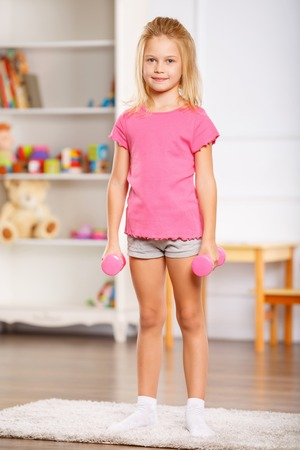 one room school house: Lovely little child is busy using small dumbbells for exercises.