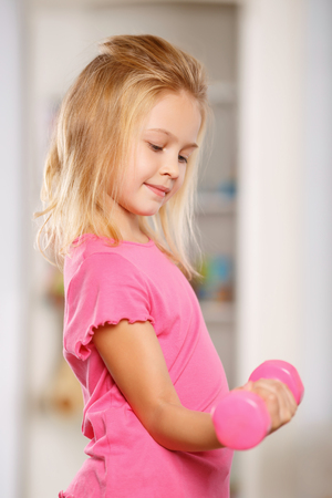 one room school house: Lovely little child is busy using small dumbbell for exercises.