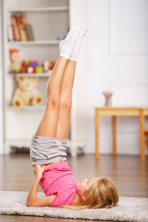 one room school house: Little schoolchild is thoroughly doing physical exercises. Stock Photo