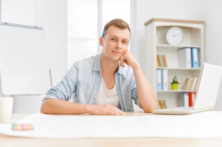 workmate: Young attractive office employee is sitting at his desk and smiling gently. Stock Photo