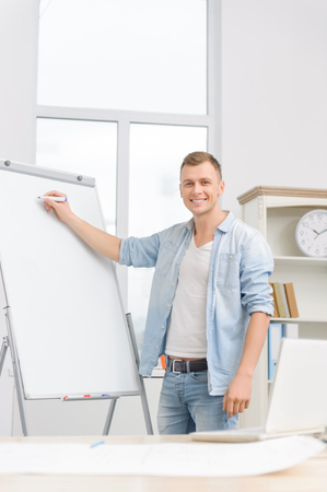 executive apartment: Handsome male member of staff is standing beside whiteboard ready to arrange a meeting. Stock Photo