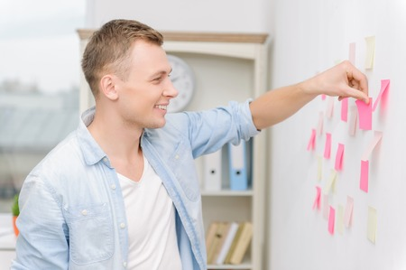 executive apartment: Nice-looking male employee is smiling brightly while attaching colorful sticky notes to the wall.
