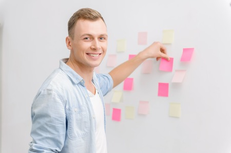 workmate: Pleasing young man is smiling radiantly while attaching small sticky notes to the wall.