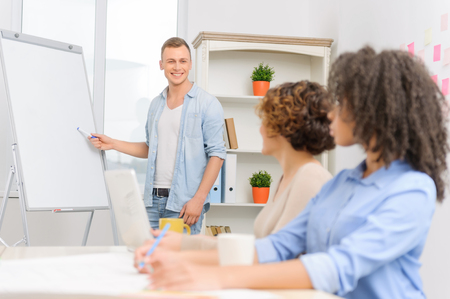 collaborators: Three positive minded colleagues are sitting in conference room and having an informal discussion.