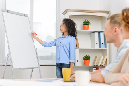 collaborators: Three positive minded colleagues are sitting in conference room and having an informal business talk. Stock Photo