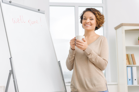 successfully: Smiling attractive young executive drinks tea after completing her task successfully.