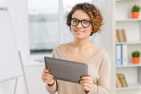 mujer trabajadora: Oficinista de sexo femenino joven est� sonriendo ligeramente mientras mantiene su tableta port�til.
