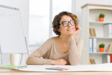 collaborator: Female white-collar worker looks happy and positive while sitting at the desk with various office supplies. Stock Photo