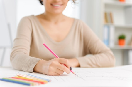 drafting: Pretty office employee is occupied with coloring her project drafting. Stock Photo
