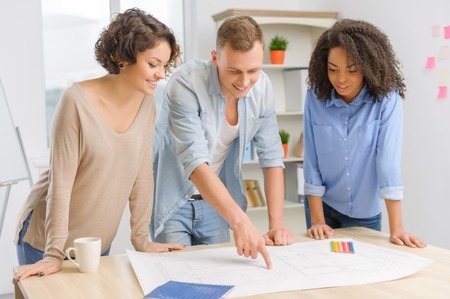 executive woman: Three young intelligent colleagues are standing beside the common table and actively discussing construction drawing.