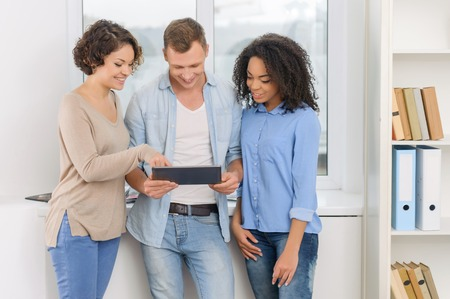 collaborators: Three young attractive people are standing near the window and analyzing digital information on portable tablet.