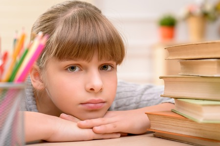 cheerless: Pleasant cheerless little girl lying on the table and going to do her homework while feeling sad