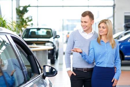 contenu Pleasant belle vente assistant montrant l'homme d'une voiture et d'exprimer la joie dans le show automobile