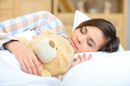 catnap: Napping with teddybear. Pleasant young teenage girl is napping while hugging her big soft teddy bear.