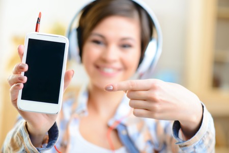 upholding: Demonstrating a device. Young smiling teenage girl is upholding her smartphone and pointing at the screen.