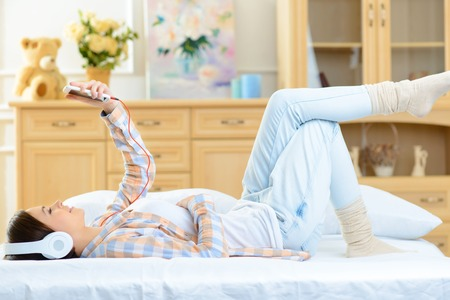 upholding: Musical hour. Appealing young teenage girl is upholding her smartphone while lying in bed and listening to music. Stock Photo