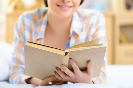 free time: Free time. Nice-looking teenage girl is smiling while lying in bed and reading a book.