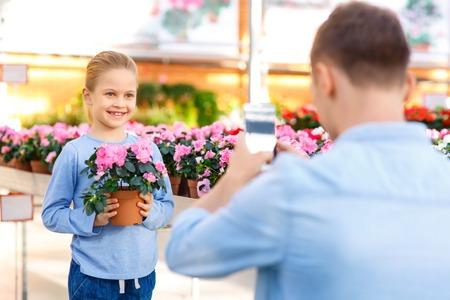 florae: Snapshot to remember. Little girl smiling and posing with flower for her father who is taking pictures on his smartphone. Stock Photo