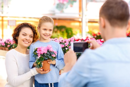 florae: Family pictures. Little girl and her mom are posing for the father who is taking pictures on his smartphone.