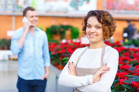 florae: Florist and customer. Smiling female florist standing and grinning while her customer having a phone talk on the background.