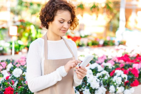 florae: Little break. Young attractive female florist is standing in the greenhouse and using her smartphone for texting. Stock Photo
