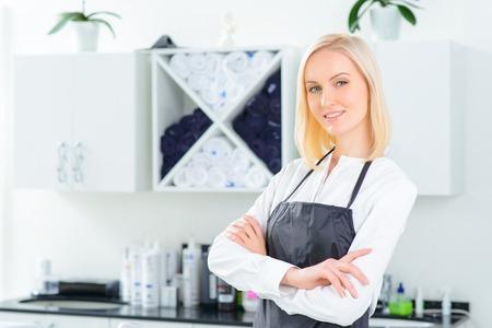 미용실에서. 매력적인 여성 미용사는 그녀의 일상 작업을 시작할 준비가되었습니다.